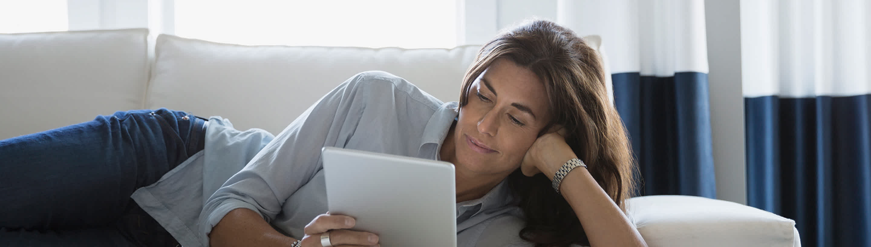 woman with a tablet lying on the couch