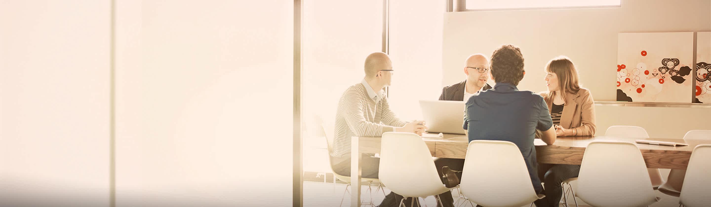 Trije moški in ženska sedijo pri mizi, imajo sestanek.
