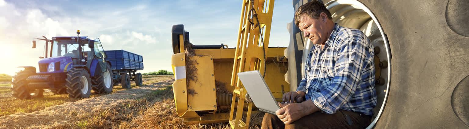 Kmetovalec počiva na kmetijskem stroju s prenosnikom v rokah