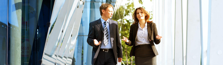 poslovnež in poslovna ženska hodita po hodniku