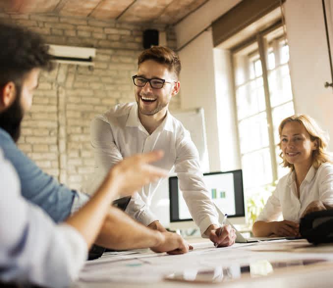 nasmejana moška in ženska sestanek pri mizi v pisarni