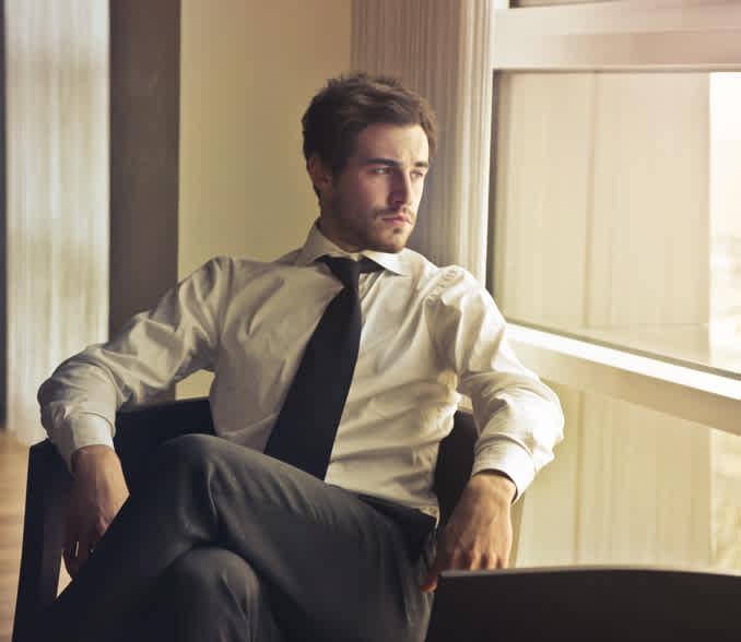 poslovnež sedi na fotelju in zre skozi okno