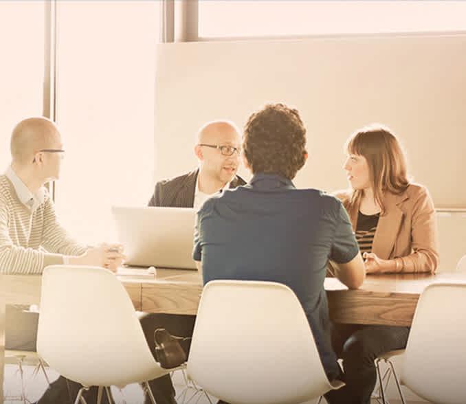 več oseb sedi pri miti, sestanek v podjetju.