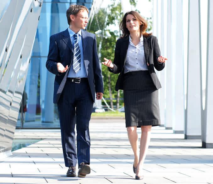 poslovnež in poslovna ženska hodita po hodniku.
