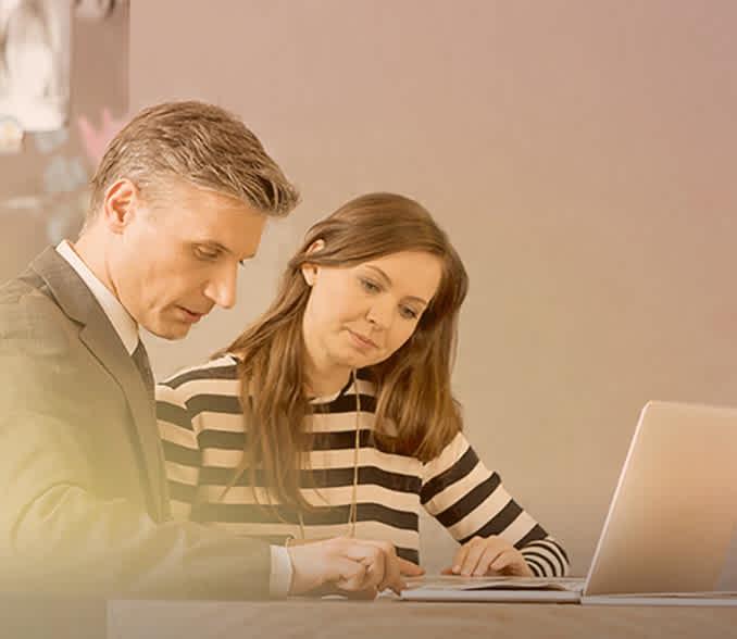 moški in ženska sedita pri prenosnem računalniku