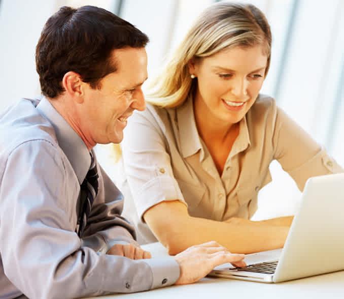 Moški in ženska spremljata vzajemne sklade na prenosniku