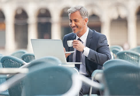 Happy man taking coffe in front of the laptop