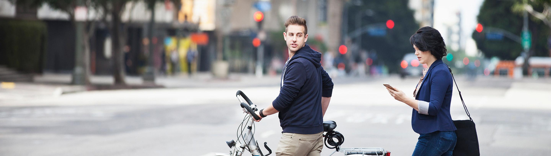 mlad par s kolesom na ulici opravlja nakazilo prek mobilnega telefona