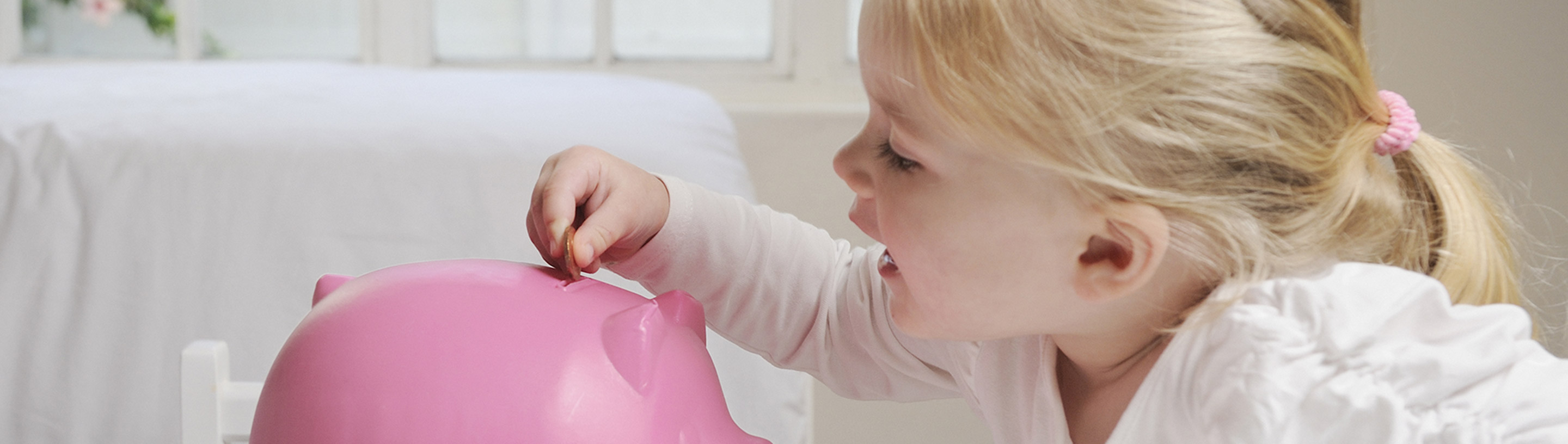 the girl puts a coin in the piggy bank