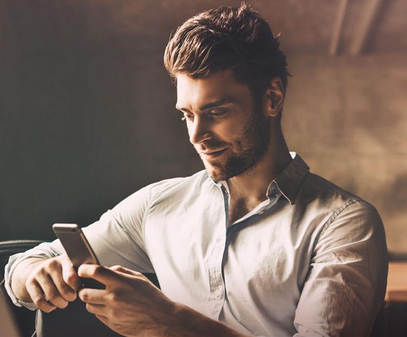 Moški v dnevni sobi spremlja kartice na svojem mobilnem telefonu