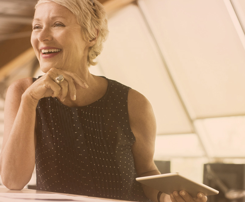 Nasmejana ženska srednjih let s tablico v roki.