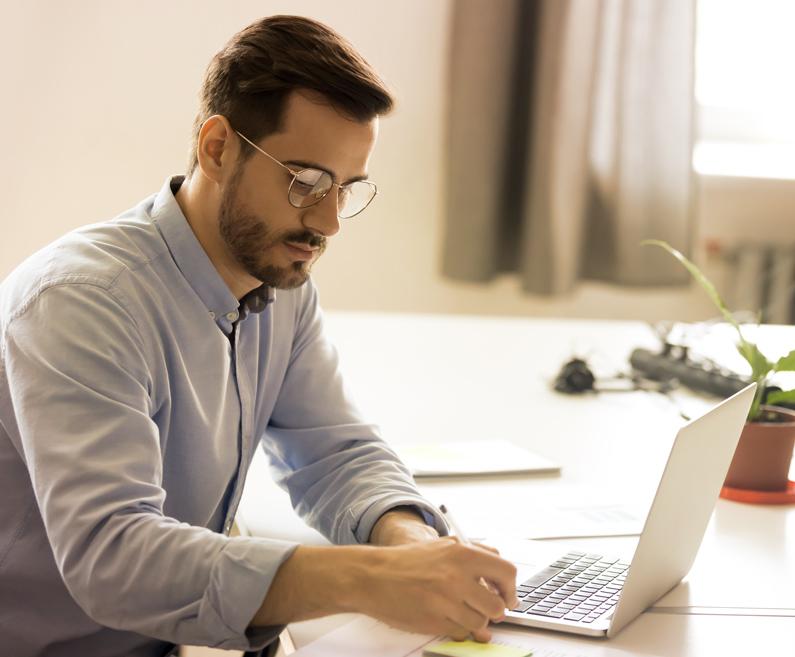 Moški z očali piše zapiske ob prenosnem računalniku.