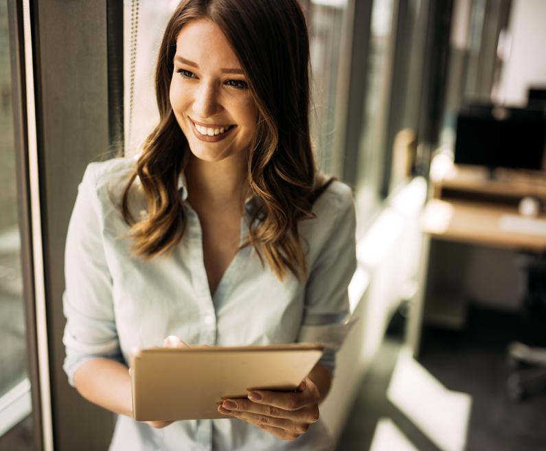 ženska s tablico v roki gleda skozi okno