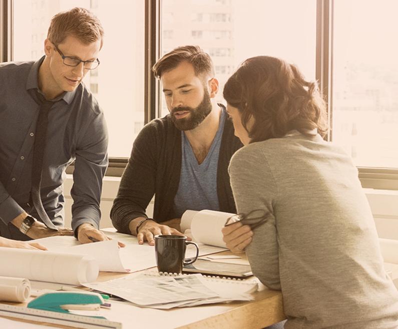 pogovor med sodelavci pri mizi, na mizi so načrti.