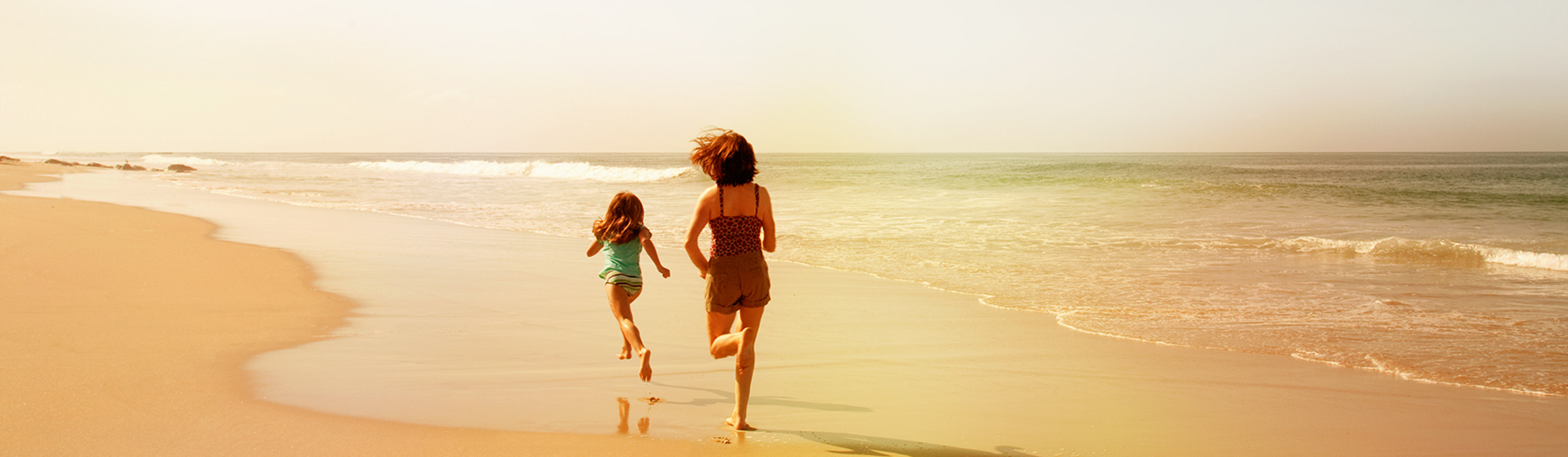 mom and daughter running down the beach