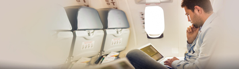Moški na letalu uporablja prenosni računalnik.