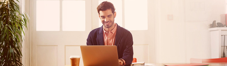 Podjetnik v pisarni dela na prenosnem računalniku