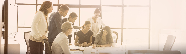 več oseb na sestanku v podjetju, ženska zapisuje na list.