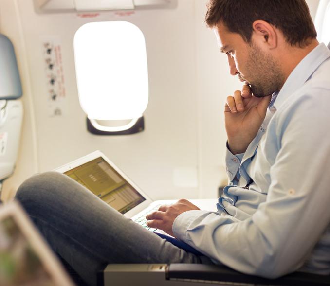 Moški na letalu s prenosnim računalnikom.