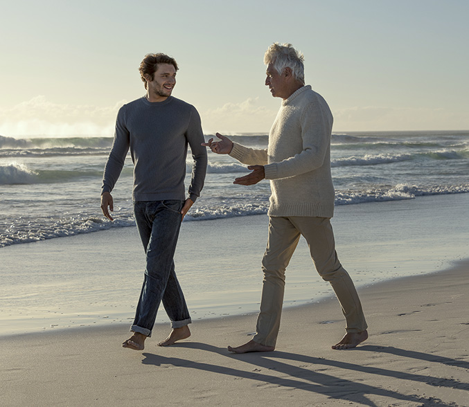 grandfather and grandson walking on the beach