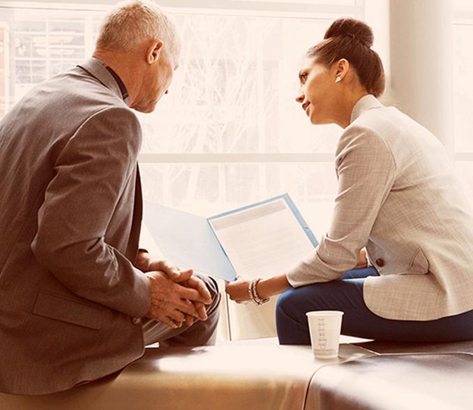 Sodelavca sedita na pisarniški mizi in debatirata o dokumentu