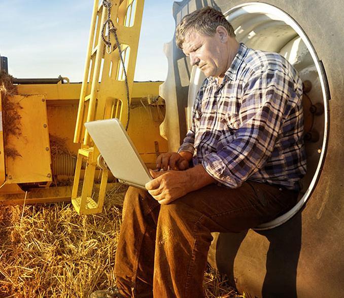 Kmetovalec na traktorju s prenosnikom v rokah