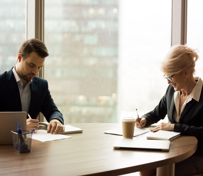 poslovna banka IN, moški in ženska podpisujeta dokumente.