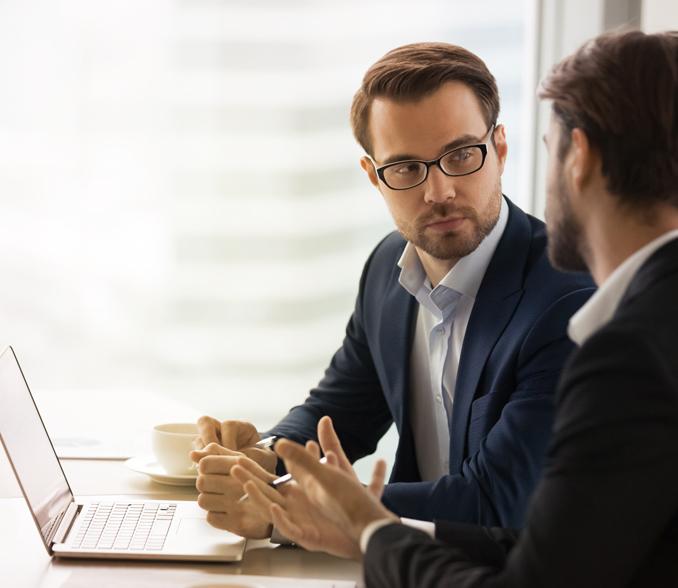 Pogovor dveh moških, pred njima je prenosni računalnik