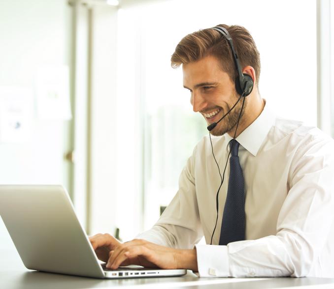 poslovnež pri računalniku s slušalkami