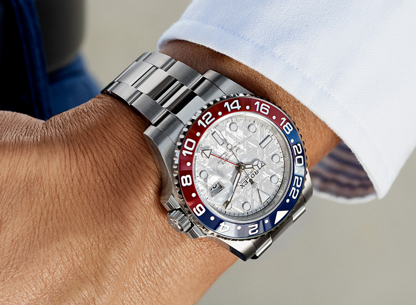 man's wrist with a rolex watch on