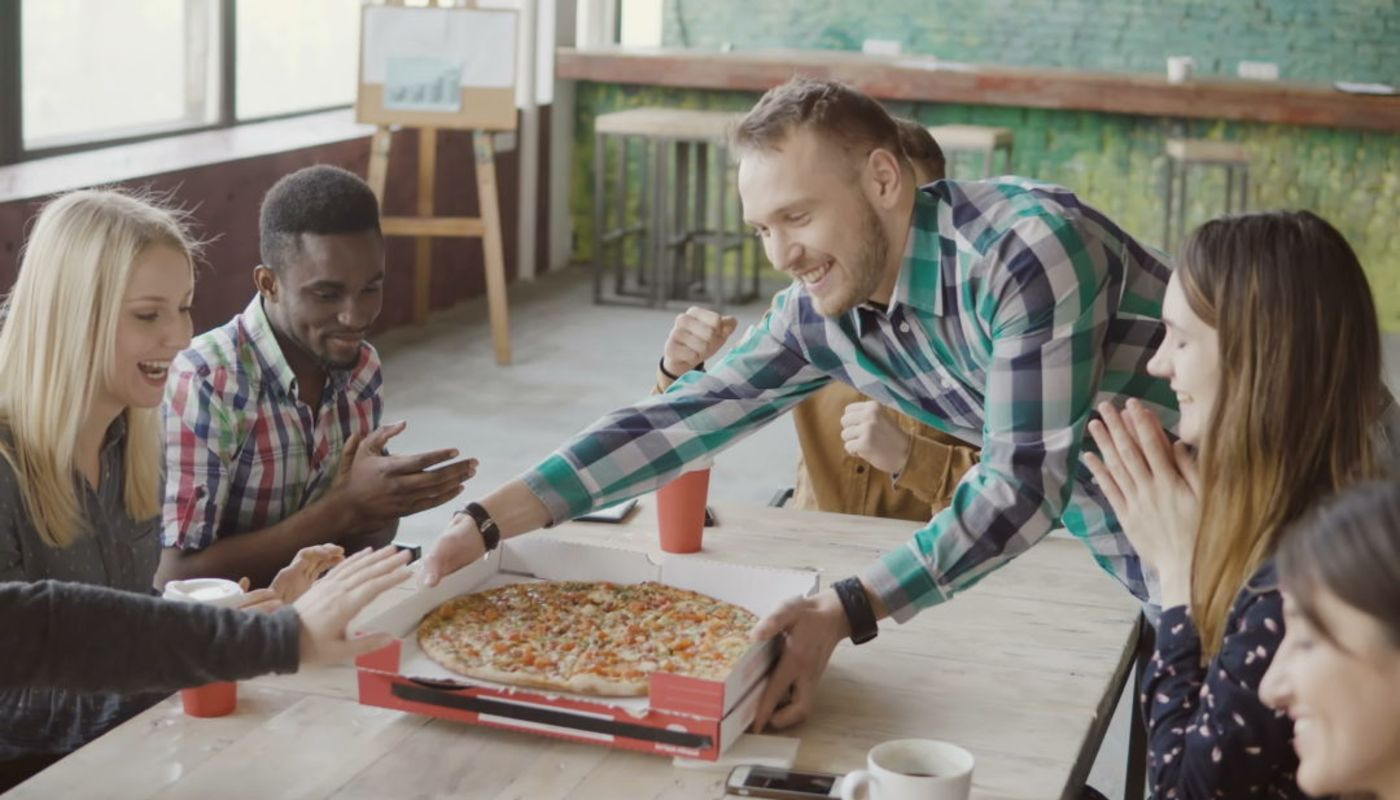 Group of very happy millennials gathered while man places two loaded pizzas on table, depicting brand persona connection.