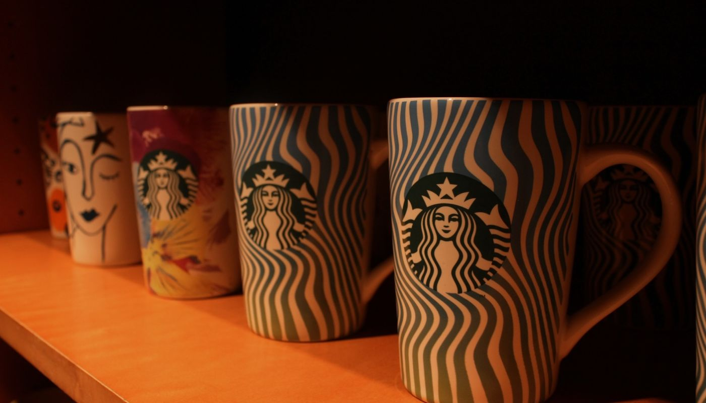 Starbuck's coffee mugs on brown shelf showing why your restaurant should start selling merchandise to remain competitive.