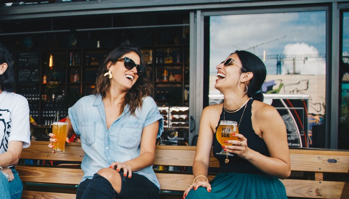 Two dark haired laughing millennial women seated outdoors on a bench holding craft beers they are loving and enjoying.