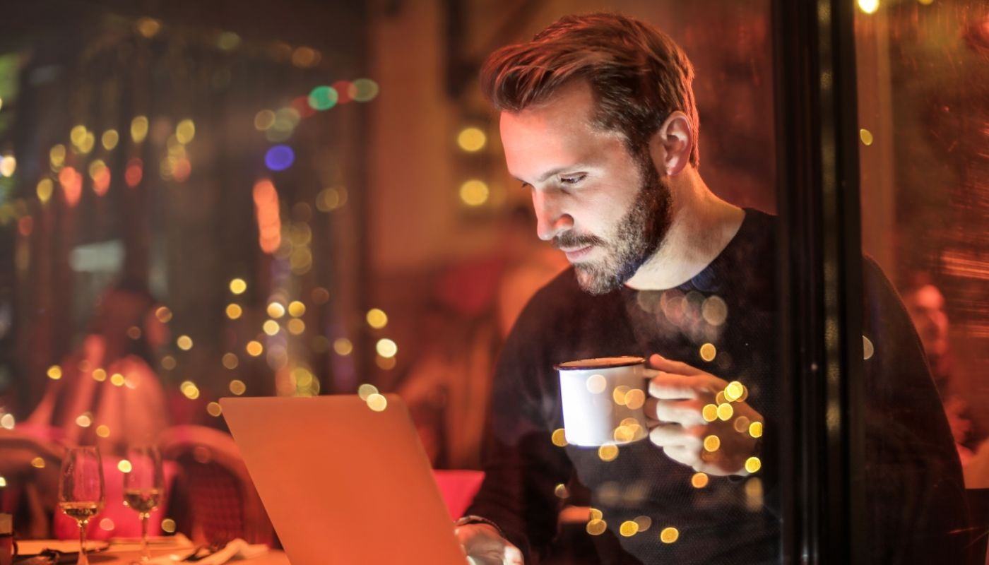 Bearded man holding coffee cup while gazing at and interacting with laptop website duplicating the restaurant's atmosphere.