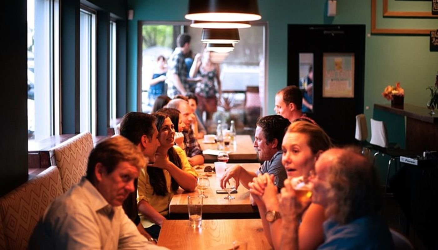 Long-shot perspective view of a very crowded restaurant showing how creative website ideas increase in-store diners.