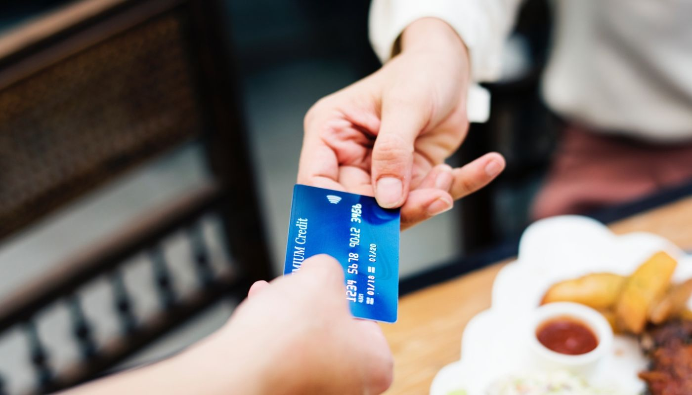 Close up of customer handing blue credit card to server, a type of payment guests prefer using to pay for restaurant meals.