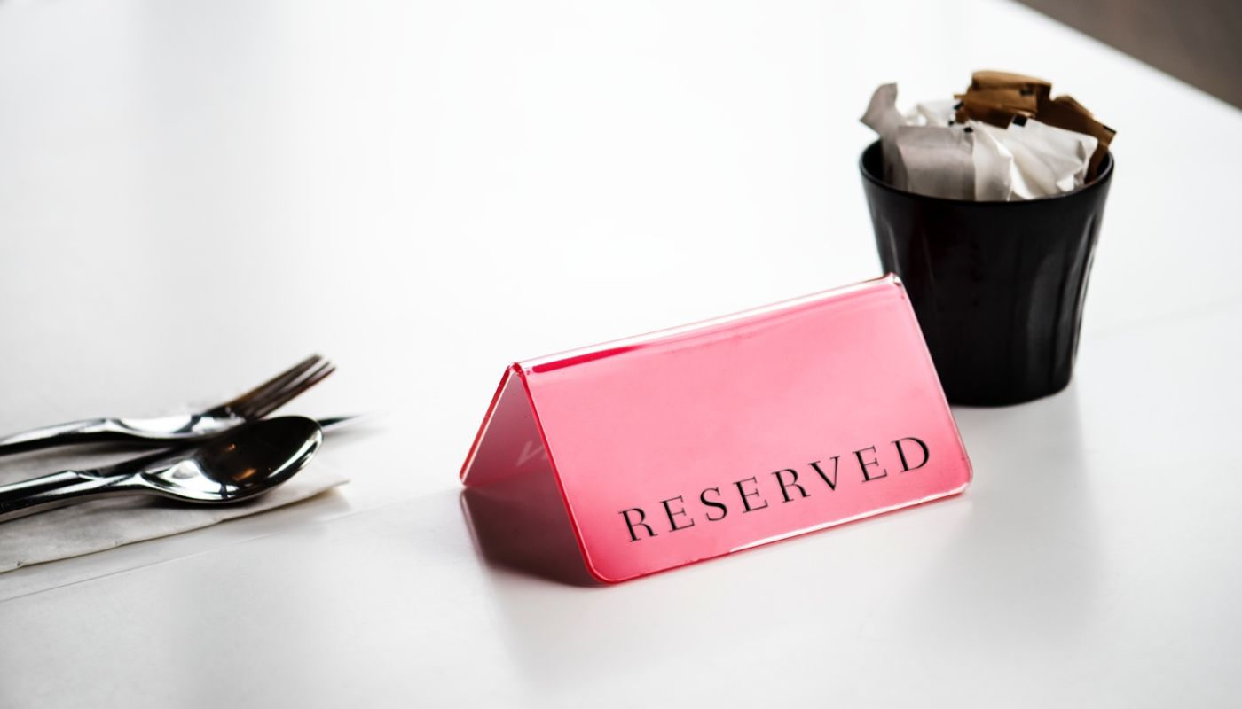 Silverware and condiments cup with red reserved sign outlining customer rewards offered complimentary by your restaurant.