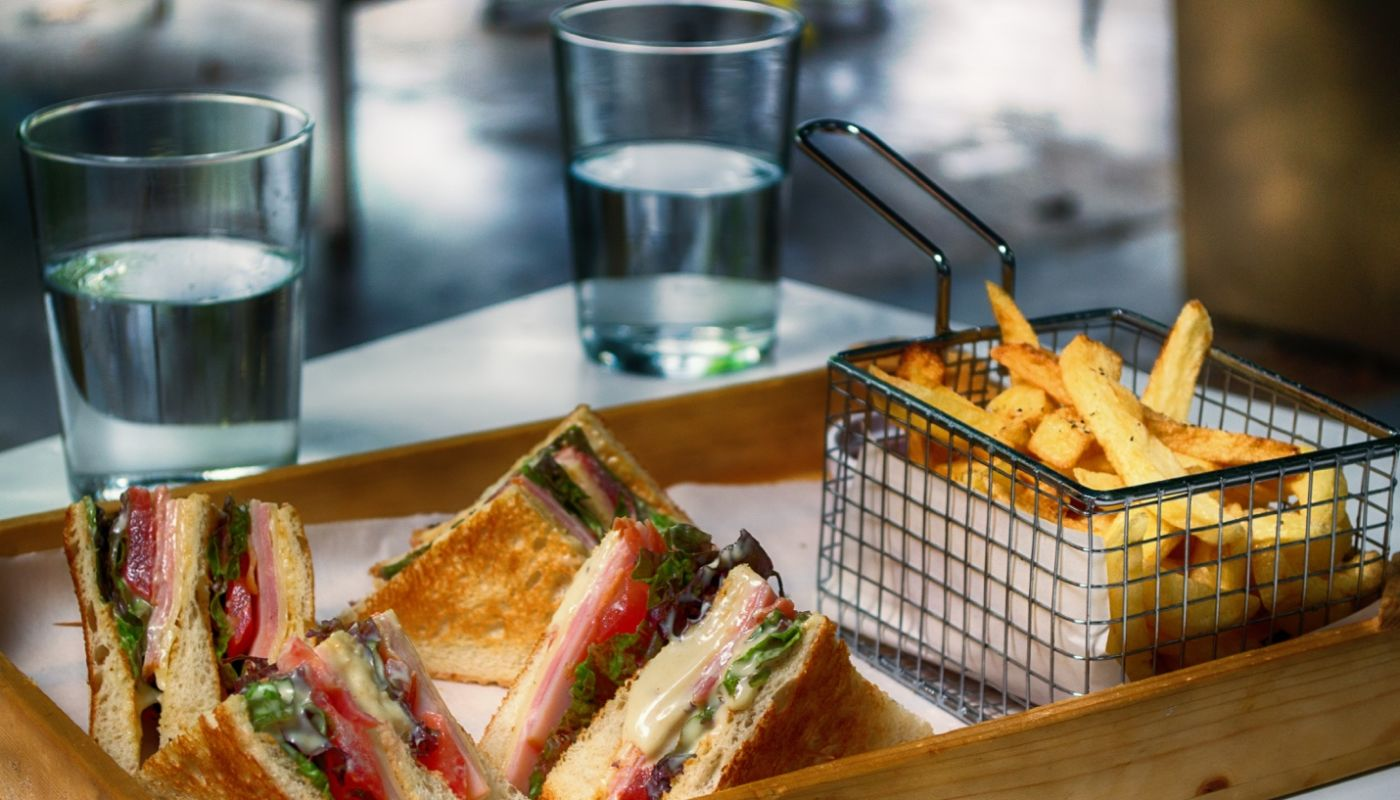 Sliced club sandwich with French fries and two glasses of water showing the integration of custom kiosks for your restaurant.