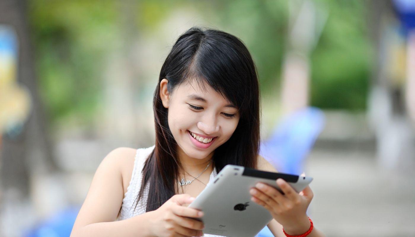 Woman with dark hair cradling tablet placing digital order, a surprising benefit of putting an interactive menu online.