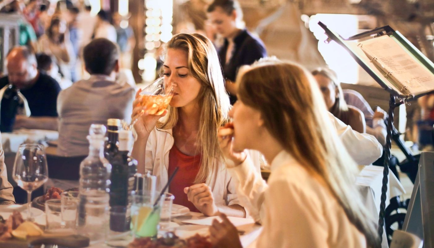 Two women at glassware-loaded table drinking and eating, an example of tracking metrics that improve customer experiences.