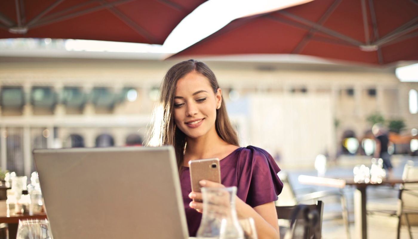 Smiling woman with brown hair holding smartphone in front of open laptop checking out restaurant rewards that customers love.