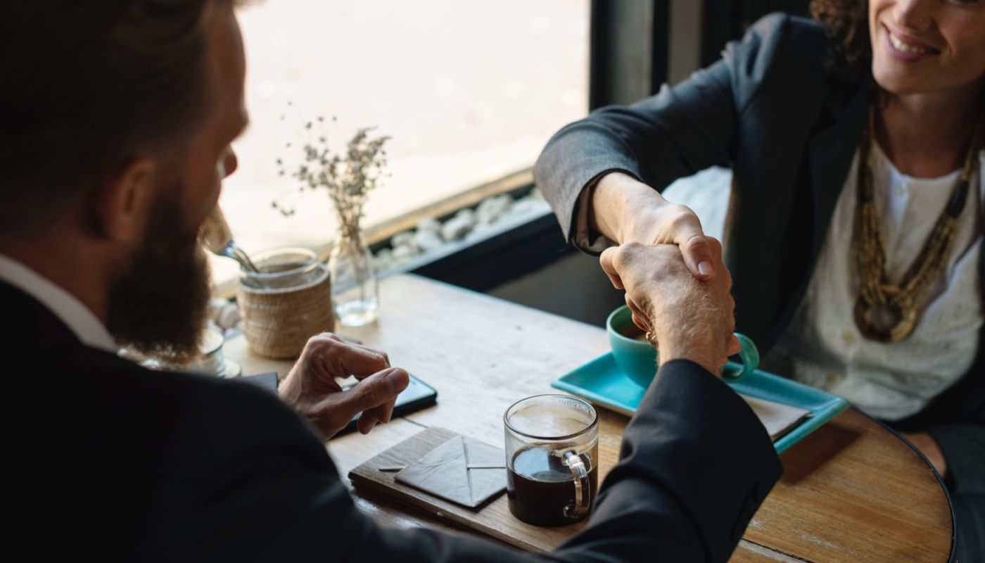 Overhead shot of man shaking the hand of a woman sitting at table showing restaurant manager found in competitive market.