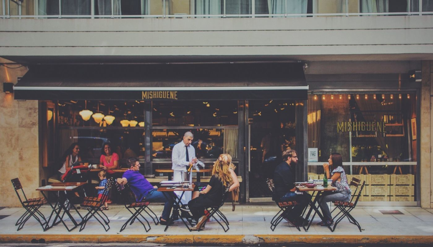 Waiter standing over group seated at table on restaurant patio appropriately handling a difficult customer situation.