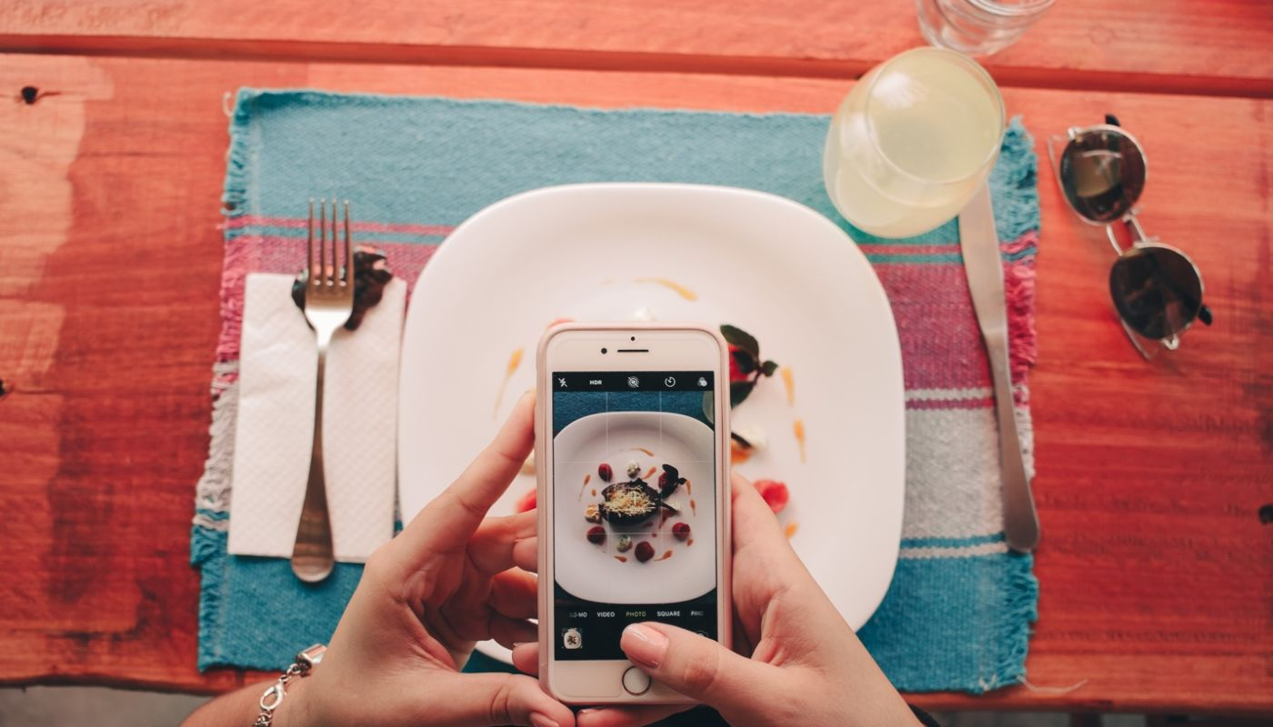 Overhead view of hands holding smartphone taking photo of food on redwood table, showing technology creating return diners.