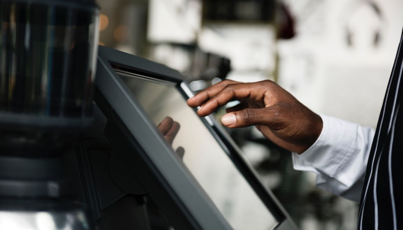 Waiter's hand touching the screen of point of sale hardware detailing the importance of API integrations for restaurants.
