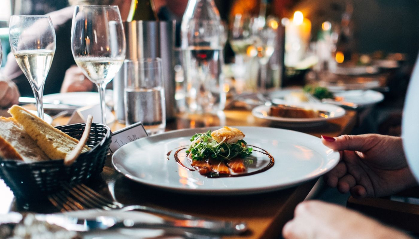 Restaurant loyalty program ideas showing hands placing plate on table laden with silverware, white dishes, and wine glasses.