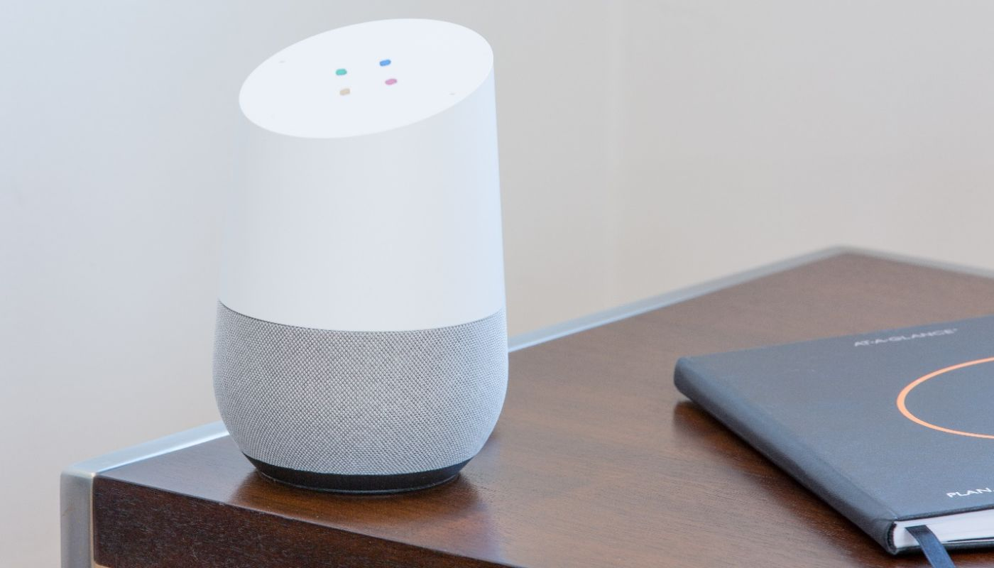Google Assistant unit ready to start capturing online orders, resting on corner of brown wood table with silver metal trim.