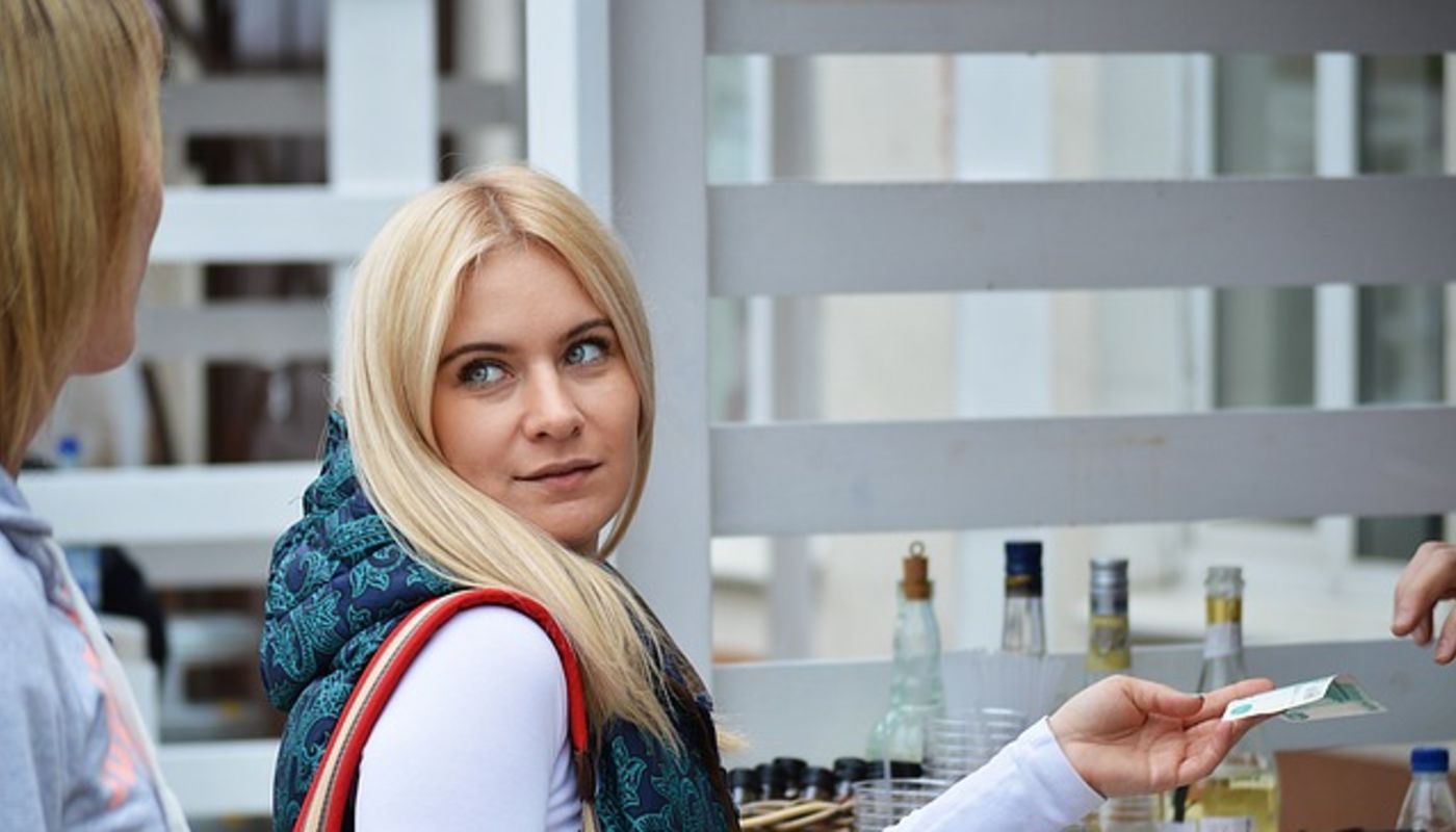 Benefiting from a loyalty plan, a blond woman gazes at her female companion while handling a rewards coupon to a server.
