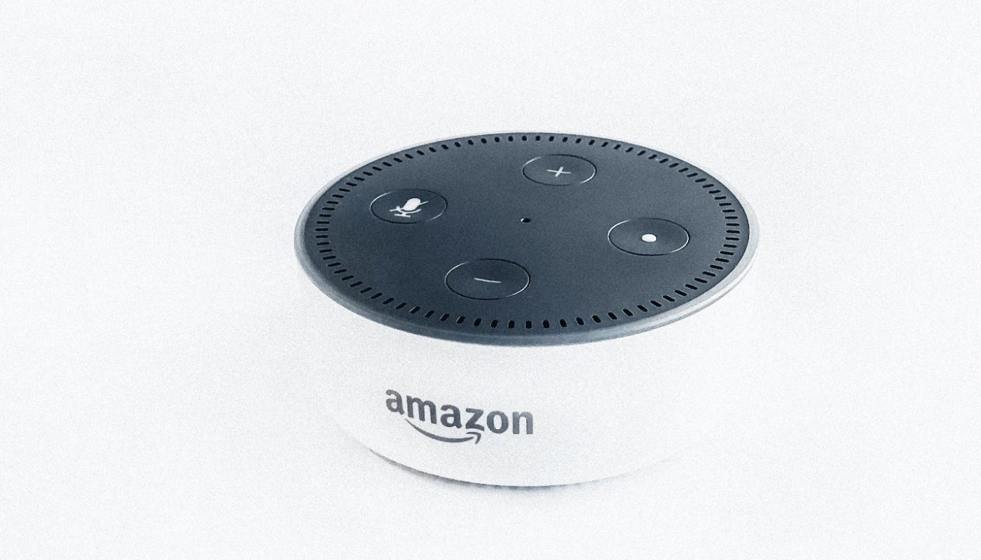 Bowl-shaped unit, white on bottom and black lid with four circular buttons to capture online orders with Amazon Alexa.