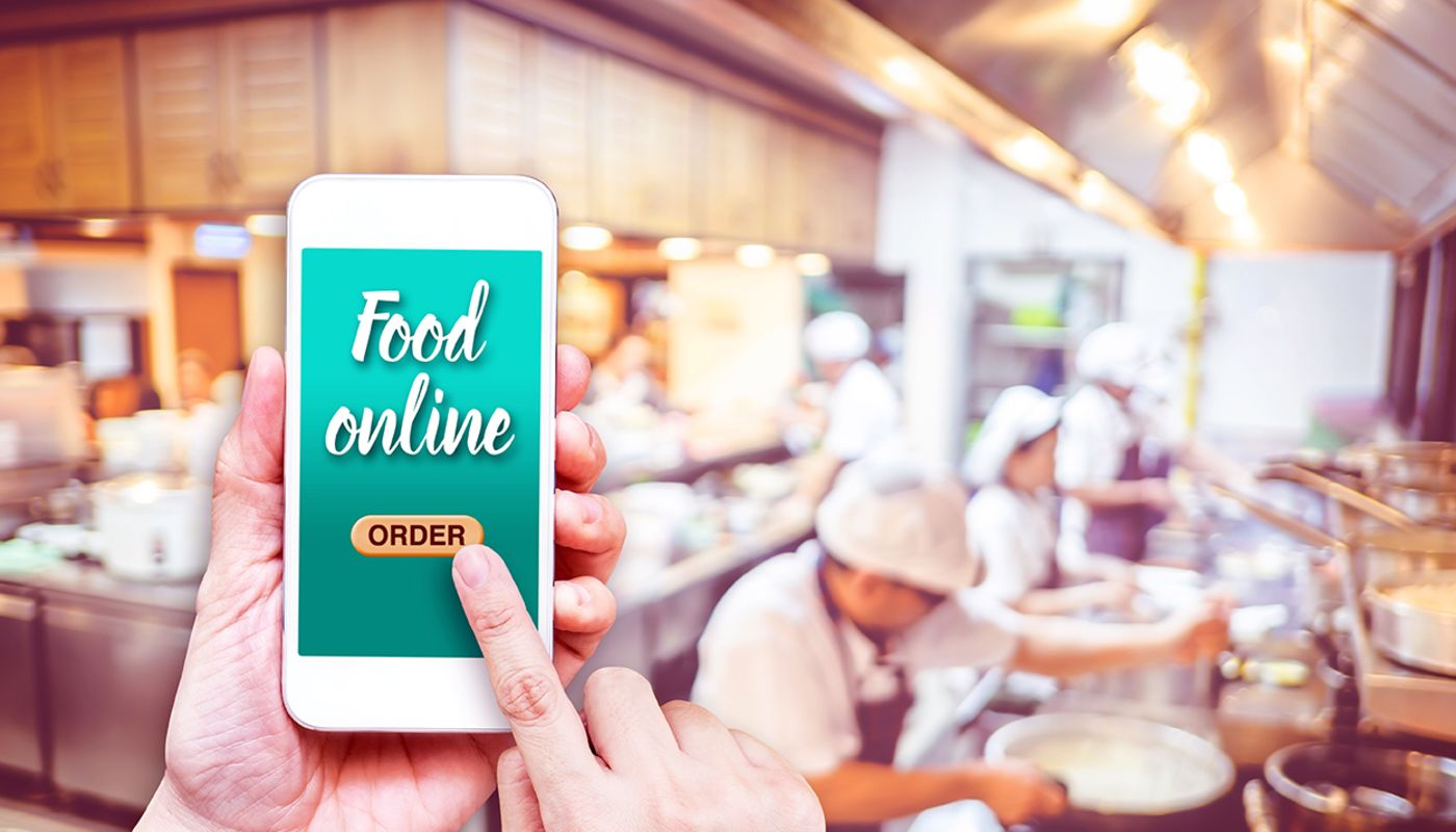 Close up of hands holding a smartphone, finger pressing online ordering button on screen in front of kitchen busy with cooks.